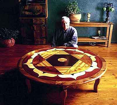 Photo: Harold Pollard poses with geometric pattern table based on tetrahedron
